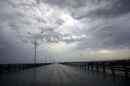 asphalt track road with a stormy dark sky background                            photo