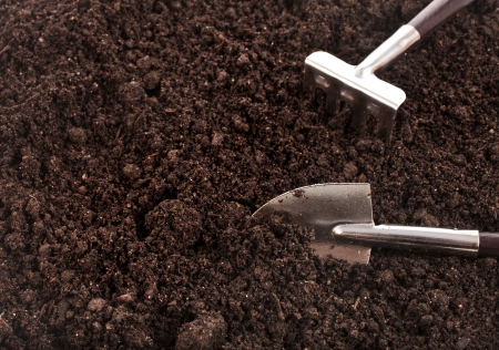 Close up of organic soil surface background with gardening tool photo
