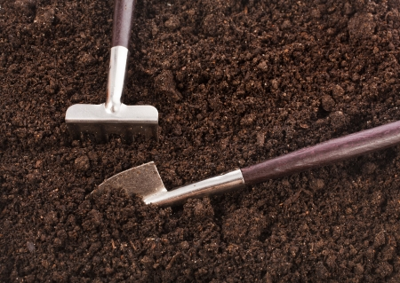 gardening tools in soil surface top view background photo