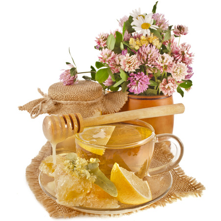 sweet flower honey in barrel and wooden drizzler in in cloth burlap napkin isolated on white background photo