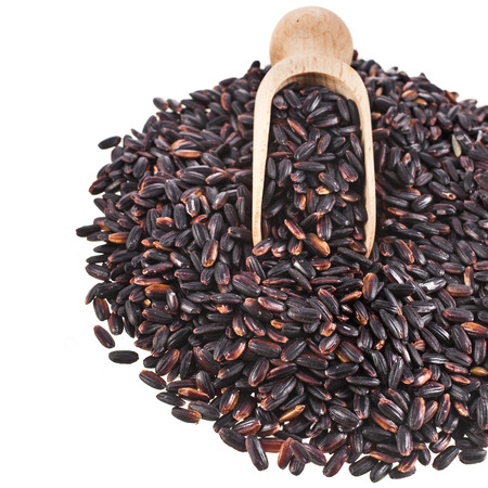 Black Rice Heap Surface Close up Macro with scoop isolated on White Background photo