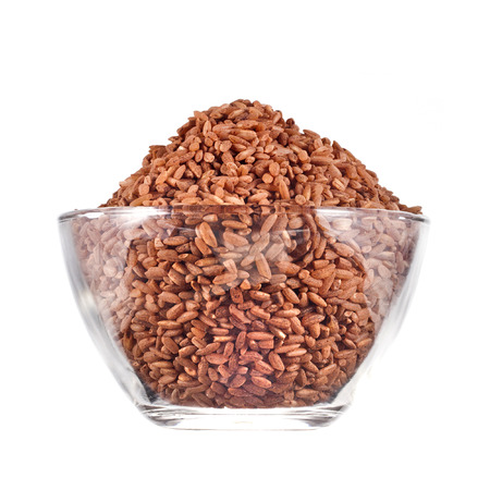 wild rice: brown rice heap in glass cup isolated on white background Stock Photo