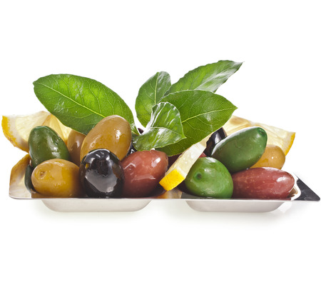 olives assortment in dish with vegetables, herbs, spices isolated on a white background photo