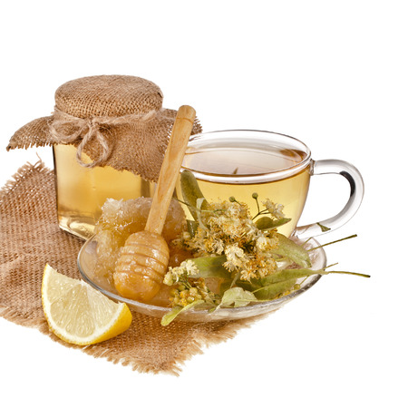 linden honey and tea cup in sackcloth isolated on white background photo