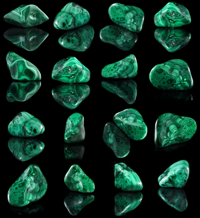 Collection set of malachite mineral stone close up with reflection on black surface background photo