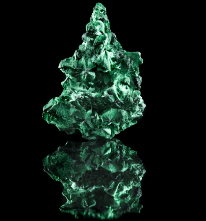 malachite mineral stone close up with reflection on black surface background Stock Photo