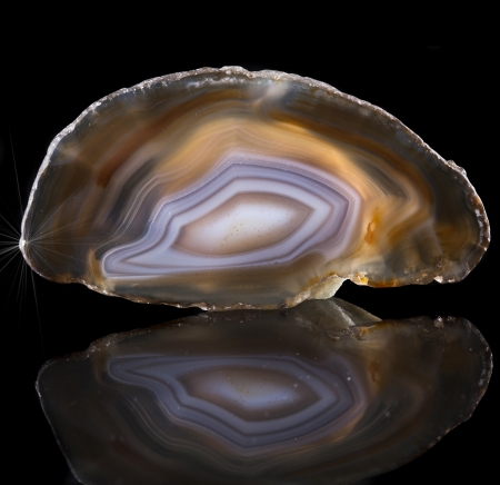 A slice of agate crystal with concentric layers on black surface background photo