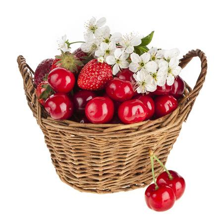 cesta de frutas: Dulce de fresa y cereza con flores en la cesta aislada en el fondo blanco