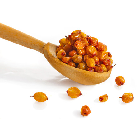 buckthorn: Dried sea buckthorn in wooden spoon close up , isolated on white background
