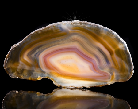 precious stone: Polished slice of agate stone crystal with reflection on black surface background