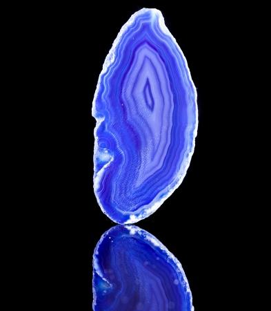 Dun plakje blauwe agaat kristallen met reflectie op zwarte oppervlakte achtergrond Stockfoto