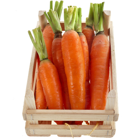 fresh carrots in a wooden crate box isolated on white photo