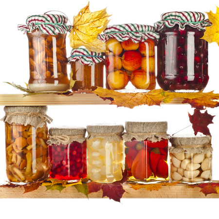 Collection of many glass bottles with homemade preserved food and autumnal colored leaves on wooden board isolated on white background photo