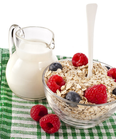 oat flake in a bowl with fresh berries and jug milk, diet concept isolated on white background photo