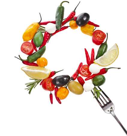 olives with vegetables and herb spice falling in fork isolated on a white background photo