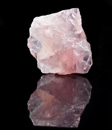 gemology: Natural Rose Quartz crystal with reflection on black surface background