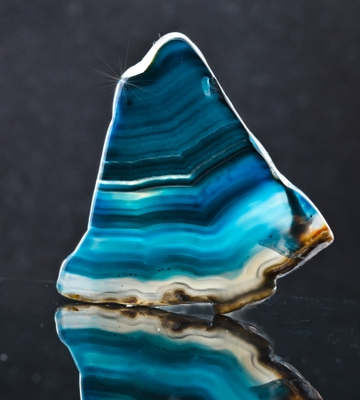 A slice of blue agate crystal with reflection on black surface background photo