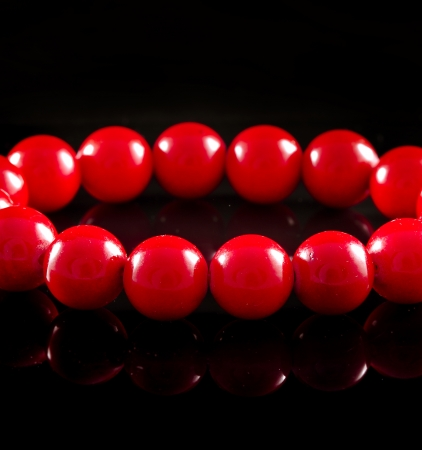 beads of red coral with reflection on black surface background photo