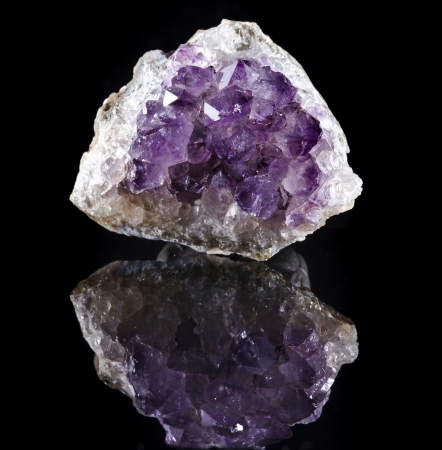 Single Natural cluster of Amethyst, violet variety of quartz close up macro with reflection on black background photo