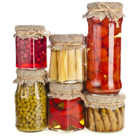 canned peas: Collection tower of many glass bottles with preserved food isolated on white background
