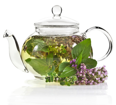 A glass tea pot with fragrant herbs isolated on a white background photo