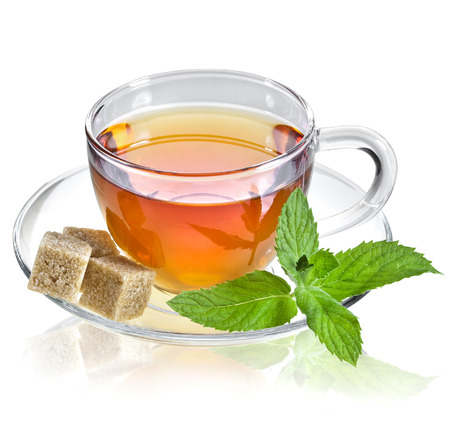 melissa: tea in glass cup with mint leaf and brown cane sugar cubes isolated on a white background
