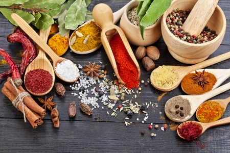 curry: Las especias en polvo en cucharas en negro fondo de la tabla de madera