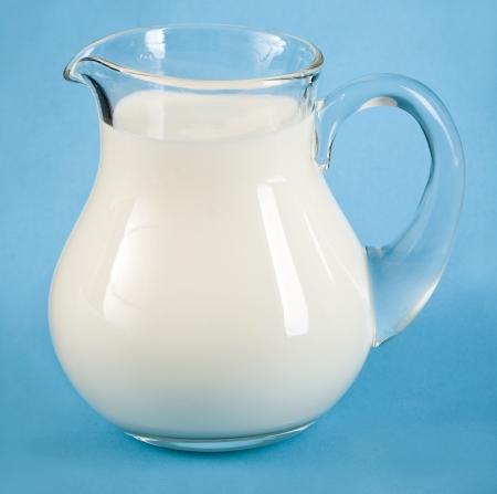 Frische Milch in Glaskanne, auf blauen Oberfläche Hintergrund