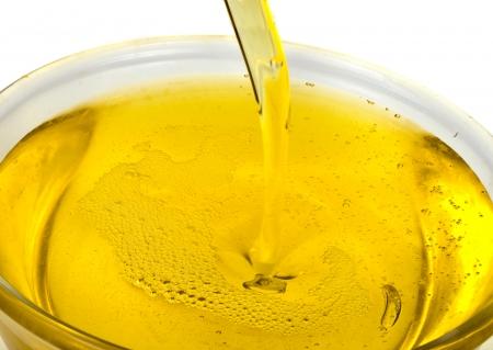 aceite de cocina: aceite de oliva vertido en un recipiente en el fondo blanco Foto de archivo