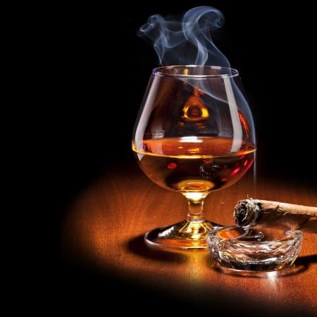 cigarro: Coñac y cigarro con humo sobre fondo negro