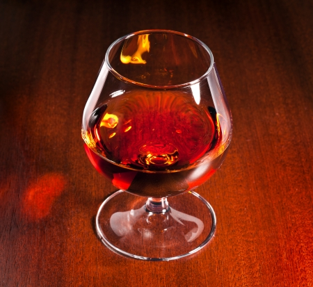 cognac: Cognac on red wooden background Stock Photo