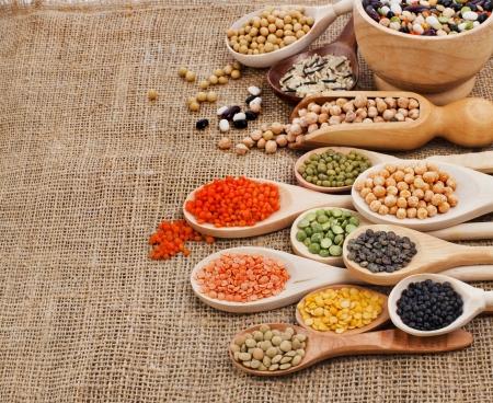 soja: vari ingredienti alimentari fagioli, legumi, piselli, lenticchie in un cucchiaio di legno sullo sfondo di sacco Archivio Fotografico