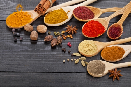 cooking utensils: Powder spices on spoons in black wooden table background