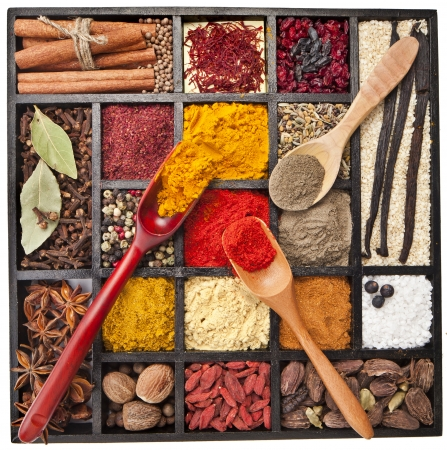 fenugreek: Assortment of powder spices on spoons in wooden box isolated on a white background