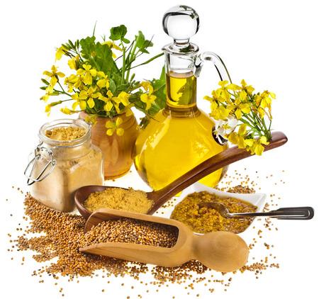 Mustard oil jar and mustard powder spoon, seeds scoop, with fresh mustard flower on white