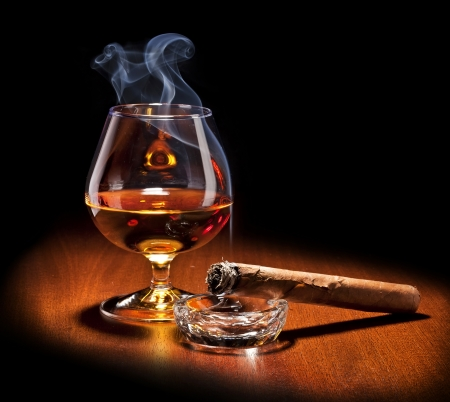 Cognac en sigaar met rook op zwarte achtergrond Stockfoto