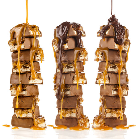Chocolate and caramel syrup poured on stack of chocolate pieces isolated on white background photo