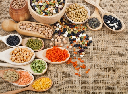 different beans, legumes, peas, lentils in spoon on the sackcloth background photo
