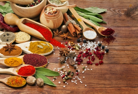 fenugreek: spices assortment on spoons in wooden background