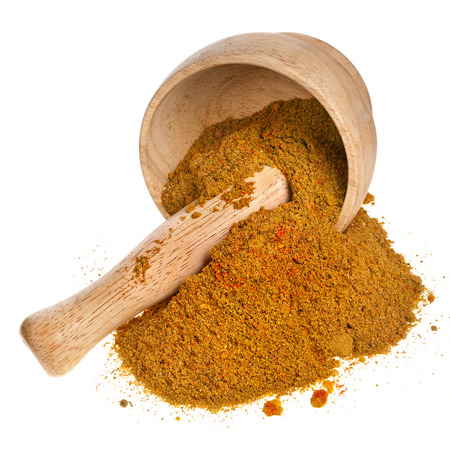 trituration: mortar with curry powder spice isolated on white background