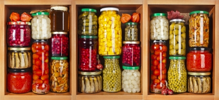 many glass bottles with preserved food set in wooden cabinet photo