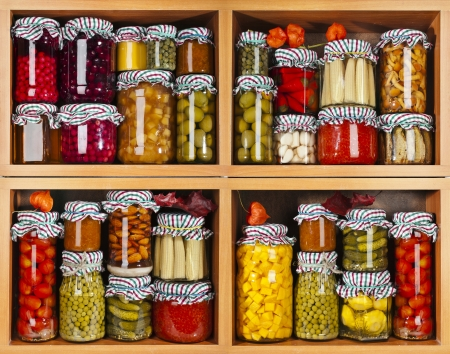 shelves: many glass bottles with preserved food in wooden cabinet Stock Photo
