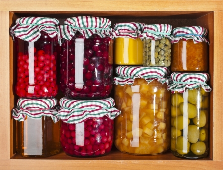 many glass bottles with preserved set food in wooden cabinet Stockfoto