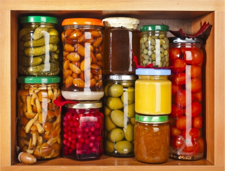 many glass bottles with preserved food in wooden cabinet Banco de Imagens