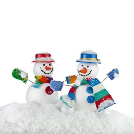 Cheerful dancing snowmans in a striped scarfs, mittens and cylinder hat isolated on white  photo