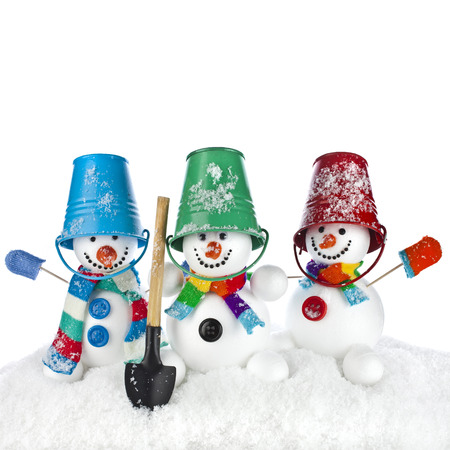 Cheerful snowman with red color bucket on his head and shovel in hand isolated on white photo