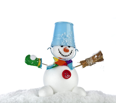 funny snowman with blue bucket and broom in hand , sitting on a snowdrift isolated on white photo