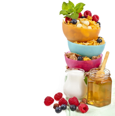 tower stack of colorful plastic bowl with fresh berries and corn flakes isolated on white background photo