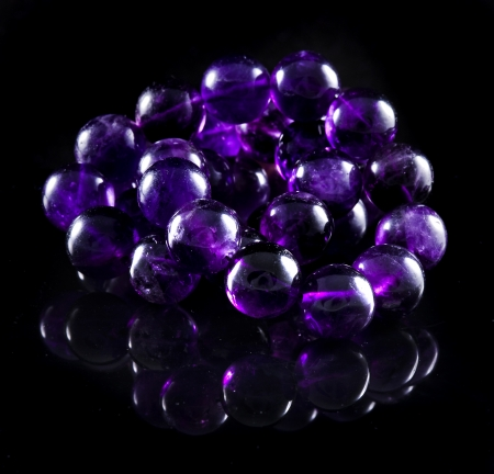 beads necklace of Natural Amethyst with reflection isolated on black surface background photo