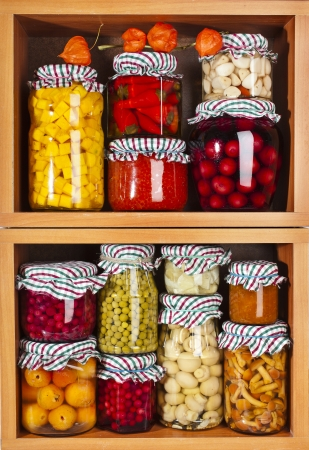 Collection of many glass bottles with preserved food in wooden cabinet photo